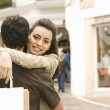 Portrait of a young couple hugging while shopping on vacation. — Stock Photo #22111427