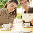Attractive couple writing postcards while sitting in a terrace coffee shop — Stock Photo