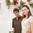 Young couple walking down a flower decorated street in south Spain. — Stock Photo