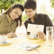 Young couple writing postcards in a coffee shop while on vacations. — Foto Stock