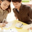 Attractive couple writting postcards while sitting in a terrace coffee shop - Stock Photo