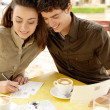 Attractive couple writting postcards while sitting in a terrace coffee shop - Foto Stock