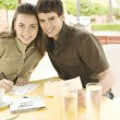 Young tourist couple writing postcards in a coffee shop while on vacations. - Stock Photo