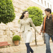 Young tourist couple holding hands and running through a town's square. — Stock Photo