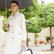 Businesswoman holding shopping bags and an open umbrella  — Stock Photo