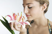 Young woman smelling a pink japanese lilly — Stockfoto