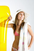 Teenage girl wearing a bikini and a hat and holding an inflatable lilo and a beach towel — Stock Photo
