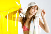 Teenage girl wearing a bikini and a straw hat and holding an inflatable lilo and a beach towel — Stock Photo