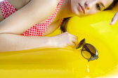 Teenage girl laying down on an inflatable yellow lilo — Stock Photo