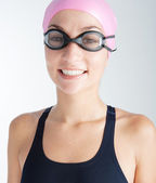 Swimmer young woman wearing a rubber hat, goggles and a swimming costume — Stock Photo