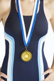Close up view of a swimmer's body wearing a gold medal. — Stock Photo
