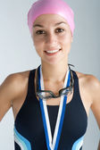 Young olympic swimmer proudly wearing a medal — Stock Photo