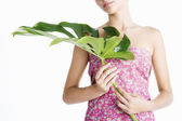 Attractive young woman holding a large green leaf in front of her — Stock Photo
