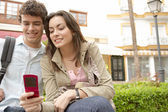 Young couple on vacations in a picturesque town square — Stock Photo