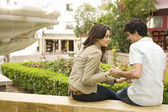 Young tourist couple sitting by fountain, holding hands and smiling. — Stock Photo