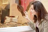 Młoda kobieta przyczajony w oknie wystawowym, aby spojrzeć na produkt — Zdjęcie stockowe