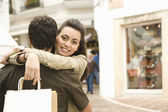 Portrait of a young couple hugging while shopping on vacation. — Stock Photo
