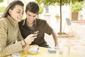 Young couple using a cell phone and writing postcards in a coffee shop — Stock Photo