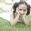 Young girl laying down on green grass — Stock Photo
