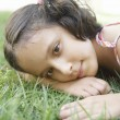Stock Photo: Young girl laying down on green grass