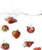 Side view of strawberries falling into clear water — Stock Photo