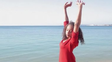 Girl stretching her arms while standing by the sea. — Stock Video