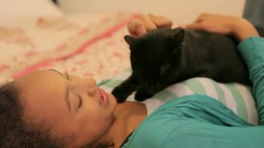 Young teenage girl caressing and stroking her black cat — Stock Video