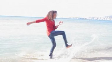 Young girl kicking sea water and turning around playfully on an idyllic beach. — Stock Video
