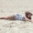 Stock Video: Girl rolling on sand of white beach.