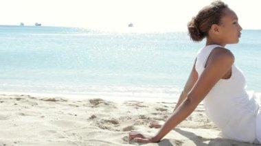 Sidovy av en tonårsflicka fastställande på en vit sandstrand — Stockvideo