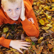 Boy with freckles laying down on leaves — Stock Photo