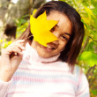 Girl holding a yellow dry autumn leaf — Stock Photo