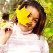 Girl holding a yellow dry autumn leaf — Stock Photo #42509451