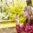 Girl in a park blowing soap bubbles — Stock Photo