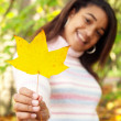 Girl holding a yellow dry autumn leaf — Stock Photo #42509613