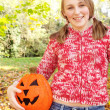 Joyful girl holding a fake halloween pumpkin — Stock Photo