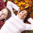 Two young girls laying on autumn leaves — Stock Photo #42509641
