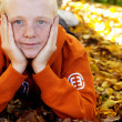 Boy with freckles laying down on leaves — Stock Photo #42509653