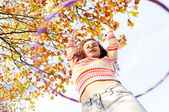 Girl playing hoola hoop in a park — Stock Photo