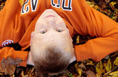 Boy with freckles laying down on leaves — Stockfoto