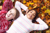 Two young girls laying on autumn leaves — Stok fotoğraf