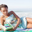 Woman reading on beach — Stock Photo