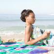 Woman listening music on beach — Stock Photo