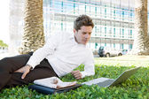 Businessman laying down on green grass — Stock Photo