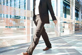 Businessman walking passed a modern glass office — Stock Photo