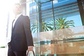Businessman in the city with a reflective modern office — Stock Photo