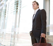 Businessman standing in the financial city district — Stock Photo