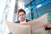 Businessman standing by a modern office building — Foto de Stock