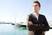 Businessman standing by a luxury yachts — Stock Photo