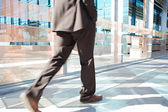 Businessman low section walking fast — Stock Photo